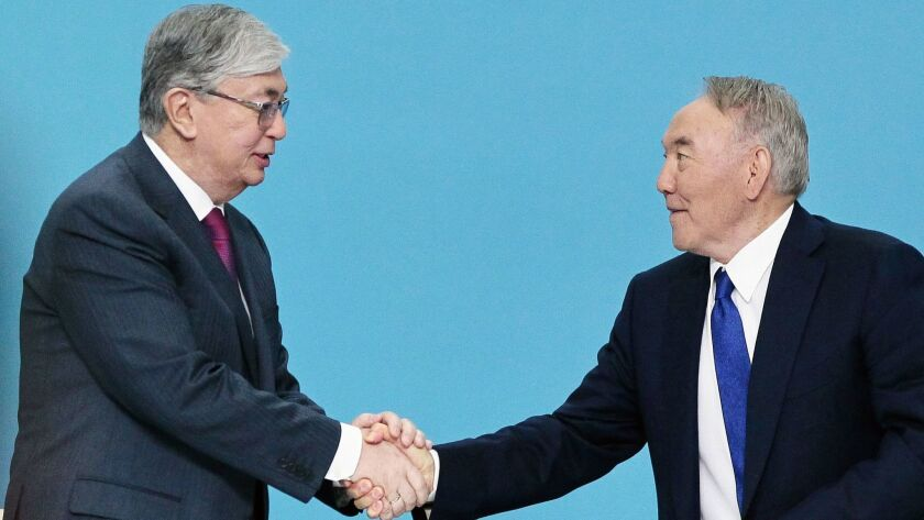 Kazakh President Kassym-Jomart Tokayev, left, shakes hands with his powerful predecessor, Nursultan Nazarbayev, during a congress of the ruling Nur Otan party in Nur-Sultan, Kazakhstan, on April 23, 2019.