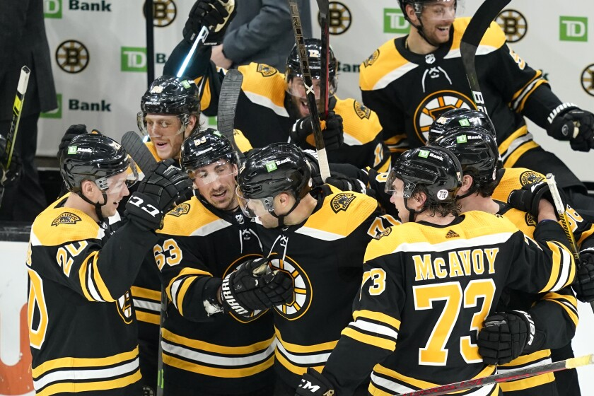Boston Bruins' Brad Marchand (63) and others surround left wing Taylor Hall, center, to celebrate his winning goal in the overtime period of an NHL hockey game against the New York Islanders, Monday, May 10, 2021, in Boston. (AP Photo/Elise Amendola)