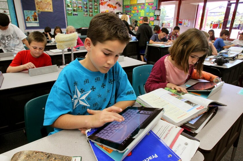 The Encinitas Union School District has outfitted some classrooms with iPads and other digital learning devices. In this photo from 2012, fourth graders Christian Quinn and Katie Eliceiri use iPads at El Camino Creek Elementary School.