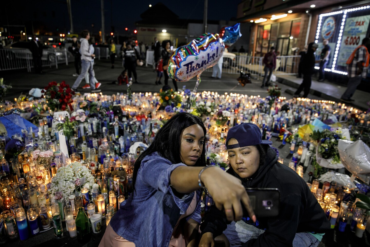 Kiara Career, left, and Tadow McReynolds, from Minneapolis, take a selfie at the Nipsey Hussle memorial outside his Marathon Clothing store in Los Angeles.