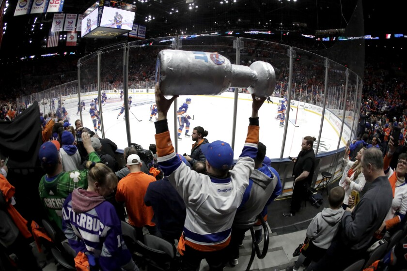 A New York Islanders fan holds a makeshift Stanley Cup during the 2019 NHL playoffs.