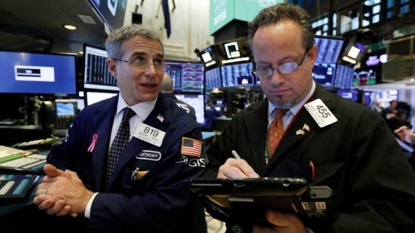 Specialist Antony Rinaldi left, and trader Robert Arciero work on the floor of the New York Stock Exchange on Nov. 9, 2018. (AP Photo/Richard Drew, File)