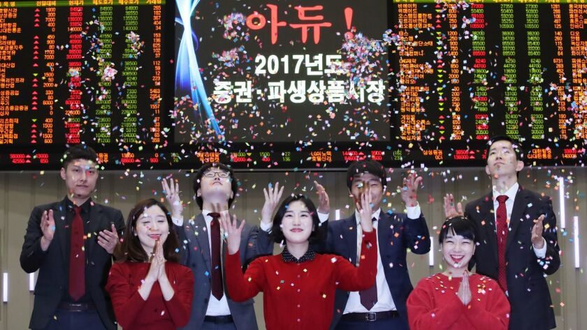 Employees applaud during a ceremony to close this year's market trading at the Korea Exchange in Seoul.