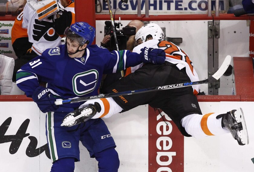 Vancouver Canucks' Jared McCann (91) checks Philadelphia Flyers' Luke Schenn during the second period of an NHL hockey game in Vancouver, British Columbia, Monday, Nov. 2, 2015. (Ben Nelms/The Canadian Press via AP) MANDATORY CREDIT