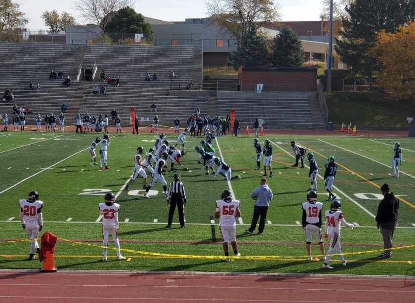 High school football players on the field, with a few scattered people watching from the stands.