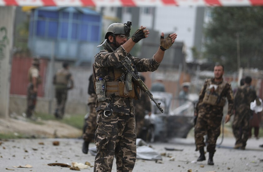 A solider holds his hands up amid rubble and other soldiers in the background