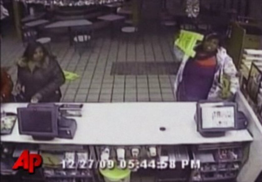 In this Dec. 27, 2009 still made from video provided by the Kansas City, Mo. Police shows a woman getting ready to throw a sign as she goes on a rampage at a McDonald's in Kansas City because she didn't like her hamburger. Police say the woman caused thousands of dollars in damage when she became upset that the restaurant wouldn't refund her money. (AP Photo/Courtesy Kansas City, Mo. Police)