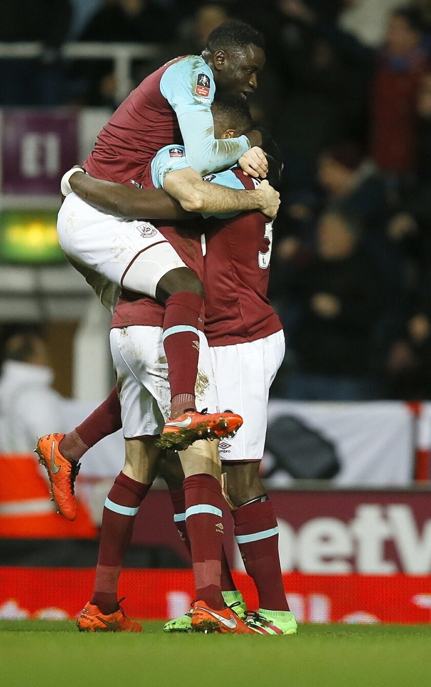 West Ham's Michail Antonio, right, celebrates scoring a goal with team mate Cheikhou Kouyate, left, during the English FA Cup fourth round replay soccer match between West Ham United and Liverpool at the Boleyn Ground stadium in London, Tuesday, Feb. 9, 2016. (AP Photo/Kirsty Wigglesworth)