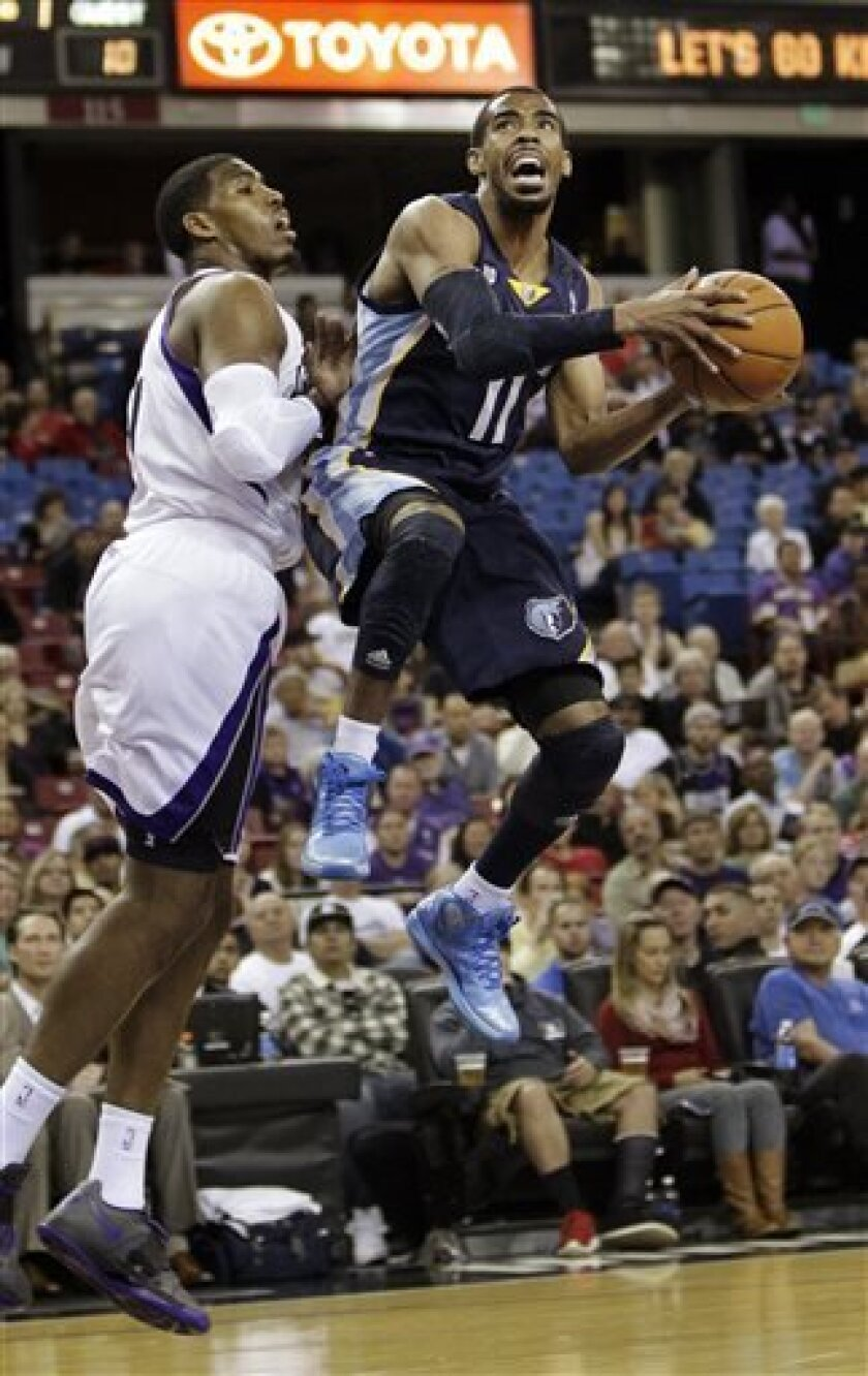 Memphis Grizzlies guard Mike Conley, right, drives to the basket against Sacramento Kings forward Jason Thompson during the first quarter of an NBA basketball game in Sacramento, Calif., Sunday, April 7, 2013. (AP Photo/Rich Pedroncelli)