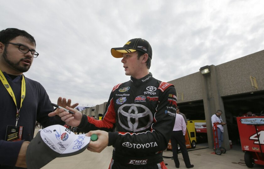 Erik Jones signs an autograph for a fan after a NASCAR Sprint Cup auto race practice at Texas Motor Speedway Friday, Nov. 6, 2015, in Fort Worth, Texas. Jones is filling in for the suspended Matt Kenseth. (AP Photo/LM Otero)