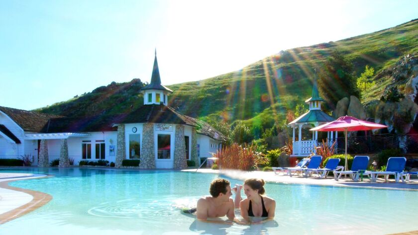 Couple on the swimming pool in front of The Spa, at Madonna Inn in San Luis Obispo.