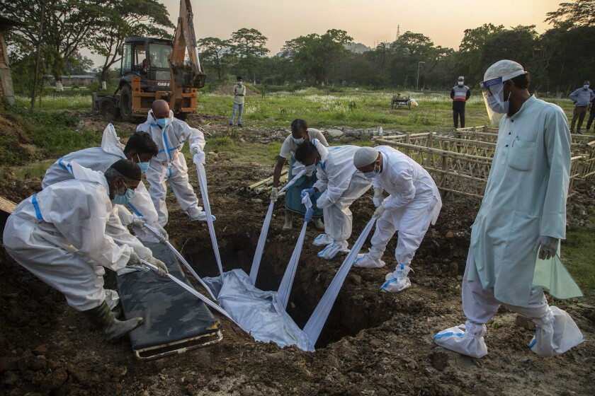 People in white Tyvek suits bury a body in India.
