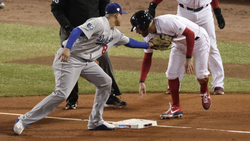 Dodgers' Manny Machado tags out Red Sox's Ian Kinsler at third base in the second inning of Game 2 of the World Series at Fenway Park on Wednesday in Boston.