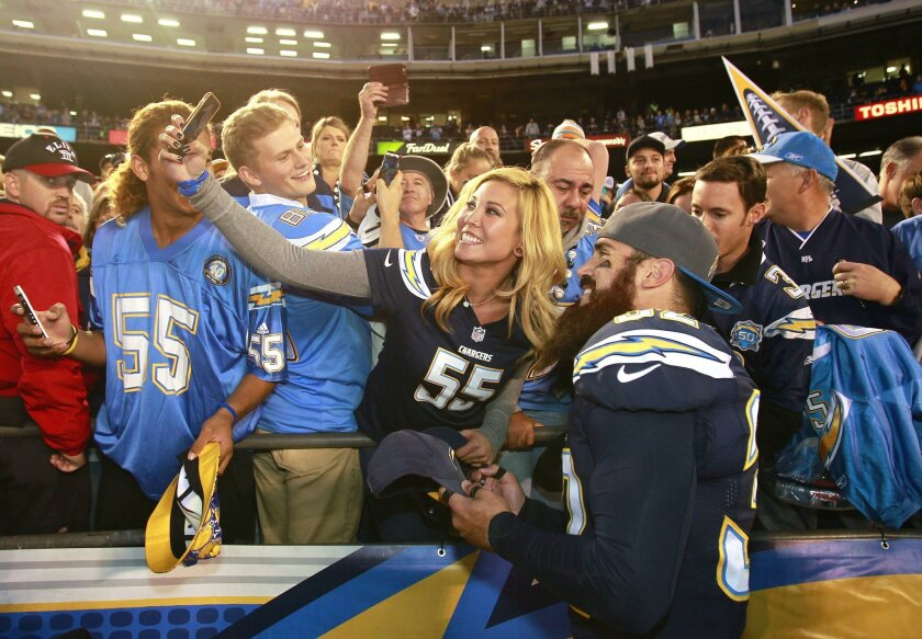 Chargers Eric Weddle takes photos with fans after a 30-14 win over Miami at Qualcomm Stadium.