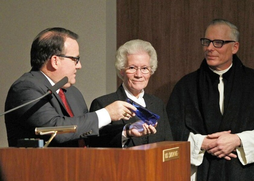 Sister Mary Vianney Ennis, center, of St. John the Baptist Catholic School proudly receives the Mayor's Award from Costa Mesa Mayor Jim Righeimer, left, during the City Council meeting Tuesday.