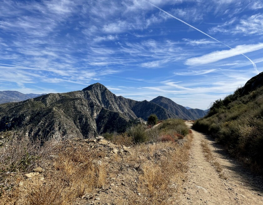View of a hiking trail through mountain peaks and blue sky