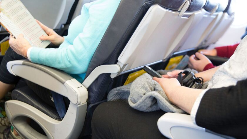 Passengers seated on an airplane are cramped in their seats