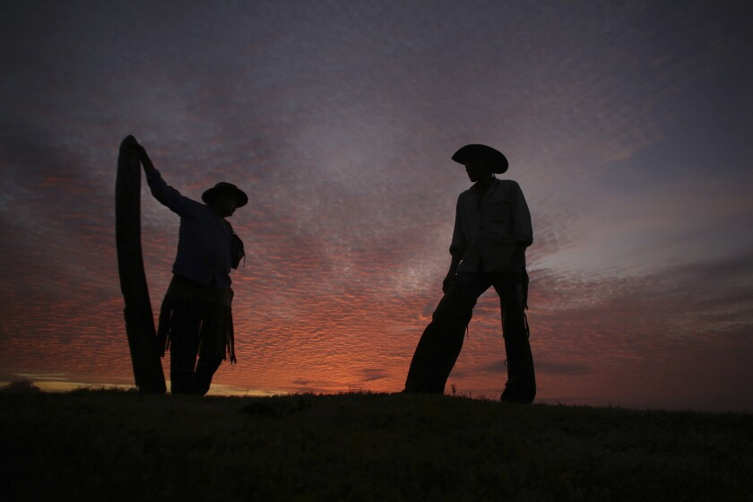 FILE - In this May 18, 2017 file photo, Joao Aquino Pereira, right, talks with fellow cowboy Rene Almeida at dawn in Corumba, in the Pantanal wetlands of Mato Grosso do Sul state, Brazil. As of Wednesday, Nov. 6 2019, fires in Brazil's Pantanal wetlands have ripped through the biodiverse region, consuming 15,000 football fields of vegetation in just the past 10 days, burning some animals alive and sending others fleeing. (AP Photo/Eraldo Peres, File)