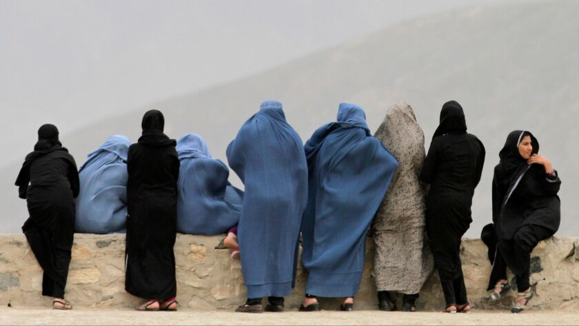 Afghani women look out over Kabul from the Naderkhan hill in Kabul, Afghanistan, Tuesday, April, 30,