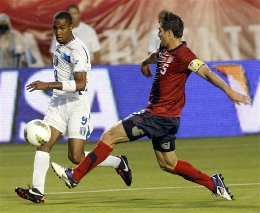 United States' Carlos Bocanegra, right, controls the ball as Honduras' Jerry Bengston, left, defends during the first half of a friendly soccer game in the rain in Miami, Fla., Saturday, Oct. 8, 2011. (AP Photo/Jeffrey M. Boan)