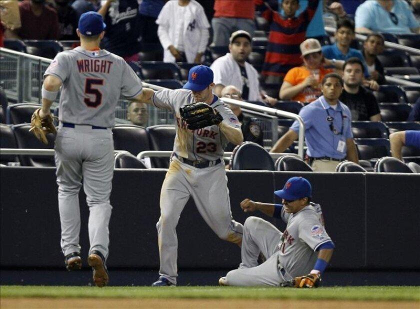El jardinero derecho de Mets Mike Baxter (c) alcanza una bola en la zona prohibida mientras su compañero Ruben Tejada (d) lo choca durante la novena entrada de un partido ante Yanquis por la MLB en el Yankee stadium, in Bronx, Nueva York (EE.UU.). EFE