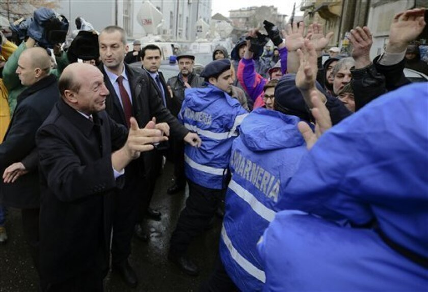 Romania's President Traian Basescu, left, speaks to supporters gathered outside a voting station in Bucharest, Romania, Sunday, Dec. 9, 2012. Millions of Romanians braved rain and snow Sunday as they went to the polls for a parliamentary election that center-left government is expected to win a, but the result could lead to more of the political instability that has plagued the impoverished Balkan nation this year. (AP Photo)