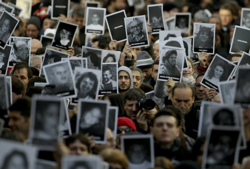 People hold up pictures of those who died in the AMIA Jewish center bombing that killed 85 people as they commemorate the attack's 22nd anniversary in Buenos Aires, Argentina, Monday, July 18, 2016. The 1994 attack is still unsolved. (AP Photo/Natacha Pisarenko)