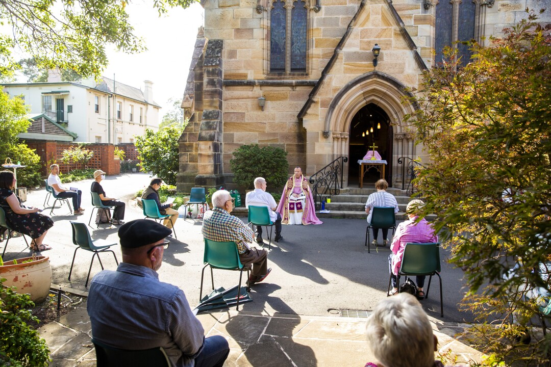 AUSTRALIA: Father James Collins holds a service in the yard of St. Paul's Anglican Church in Burwood with seating observant of social distancing in Sydney, Australia. Churches across Sydney have opted to suspend services or hold them outdoors in response to the pandemic.