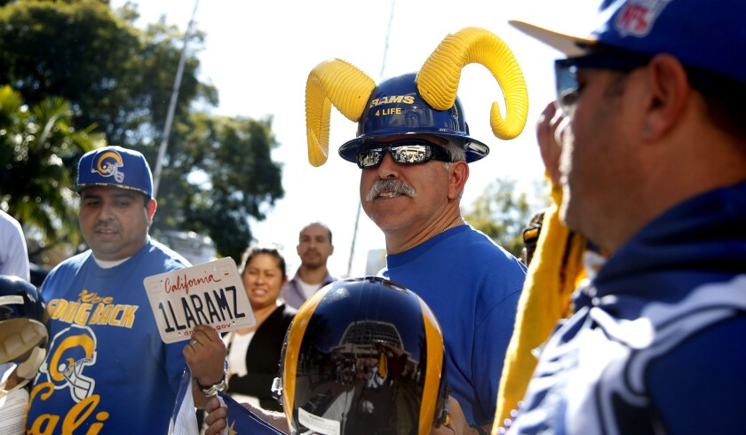 Rams fans (from left) Daniel Palma of Fullterton, Joe Ramirez of Los Angeles, and Skye Sverdlin of Venice attend a news conference held by Inglewood Mayor James T. Butts to discuss a new proposal to incorporate an 80,000-seat sports stadium in a development project at Hollywood Park.