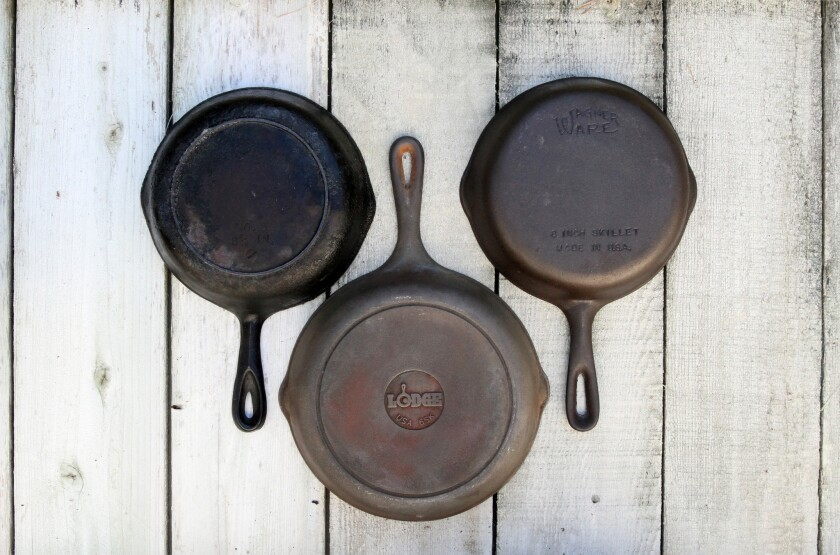 An old, neglected cast iron skillet, left, one that has just been stripped as part of the restoration process, center, and a freshly seasoned pan refurbished by Joseph Shuldiner.