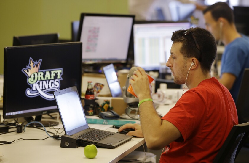 Devlin D'Zmura, a tending news manager at daily fantasy sports company DraftKings, works on his laptop at the company's offices in Boston.