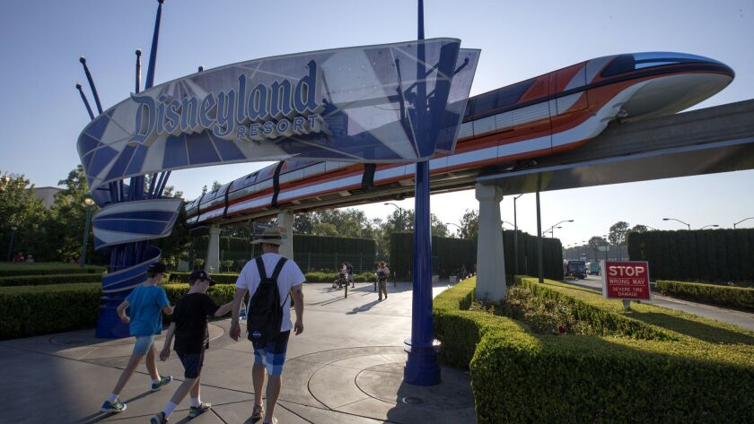 Visitors walk under a Disneyland sign at the theme park in Anaheim. Disney, through a subsidiary, has spent heavily on the upcoming Nov. 6 election in Anaheim.