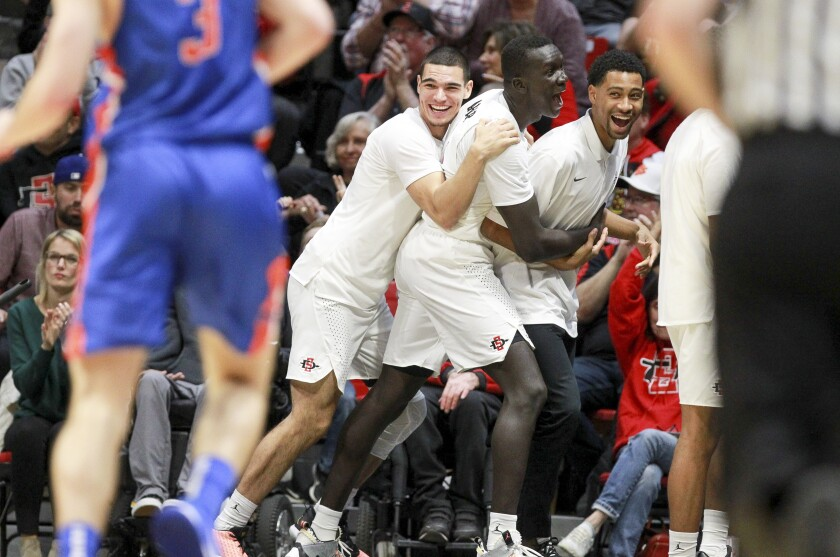 SDSU's Caleb Giordano (left) and Aguek Arop (center) celebrate with teammates after a 3-point shot by teammate Malachi Flynn in Saturday's 83-65 win against Boise State.