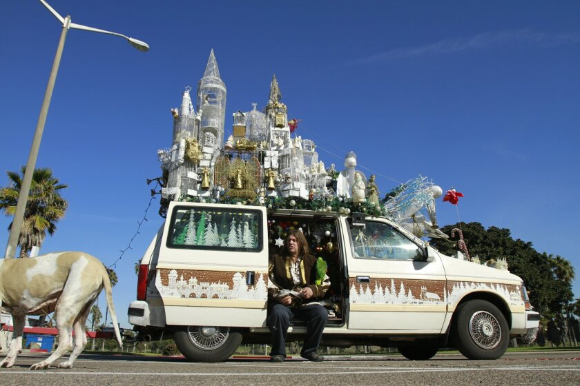 """Larry Bogaert with his holiday-season """"art car,"""" which is also where he sleeps."""
