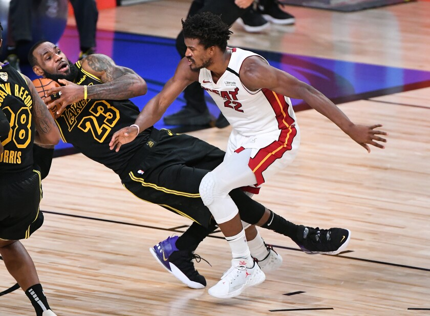 Lakers forward LeBron James collides with Heat forward Jimmy Butler during the fourth quarter of Game 5 on Friday night.