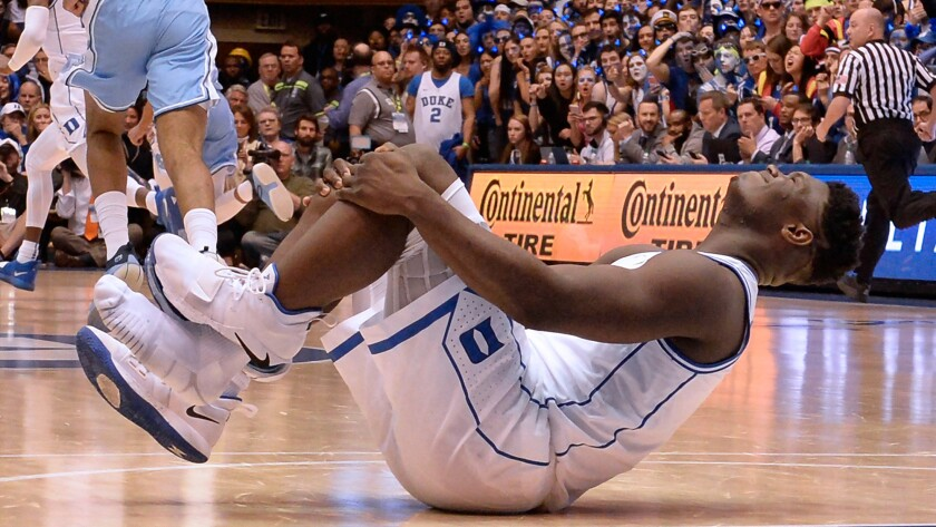 Duke forward Zion Williamson grimaces after injuring his right knee during a game against North Carolina on Feb. 21.
