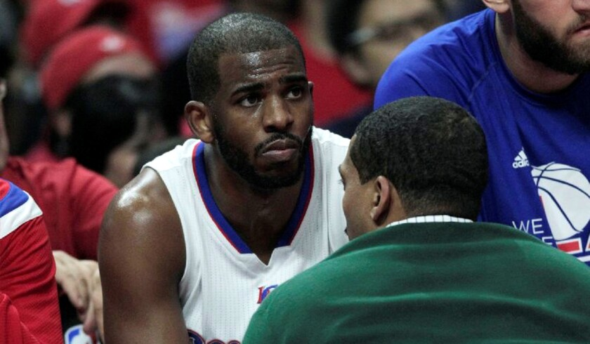 Clippers guard Chris Paul is tended to by a team trainer after hurting his hamstring in the first quarter against the Spurs in Game 7 of the first round of the playoffs.