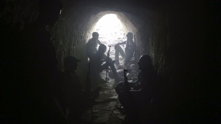 Syrian rebel fighters hold a position inside a tunnel in Ain Tarma, in the eastern Ghouta area, a re