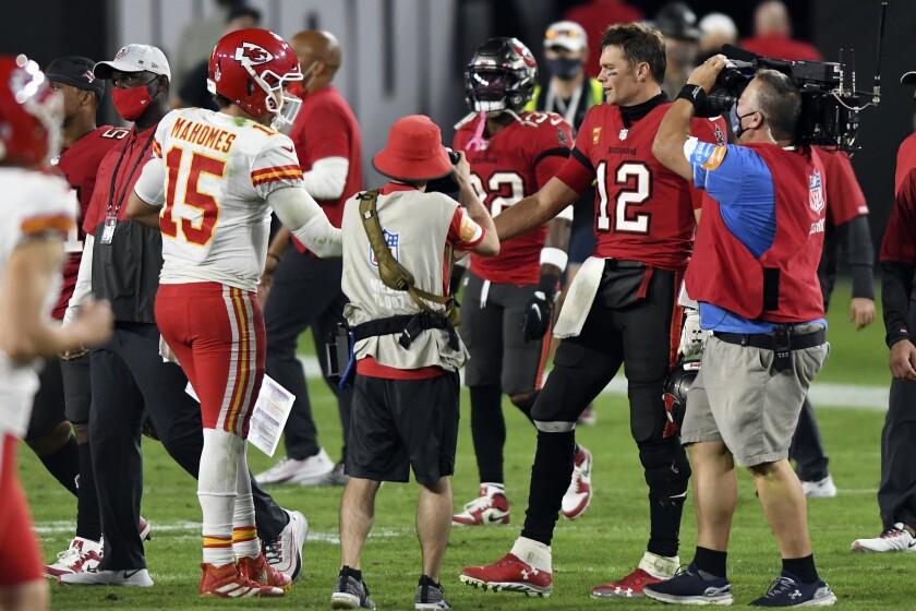 Tampa Bay Buccaneers quarterback Tom Brady (12) congratulates Kansas City Chiefs quarterback Patrick Mahomes (15) after their NFL football game Sunday, Nov. 29, 2020, in Tampa, Fla. (AP Photo/Jason Behnken)