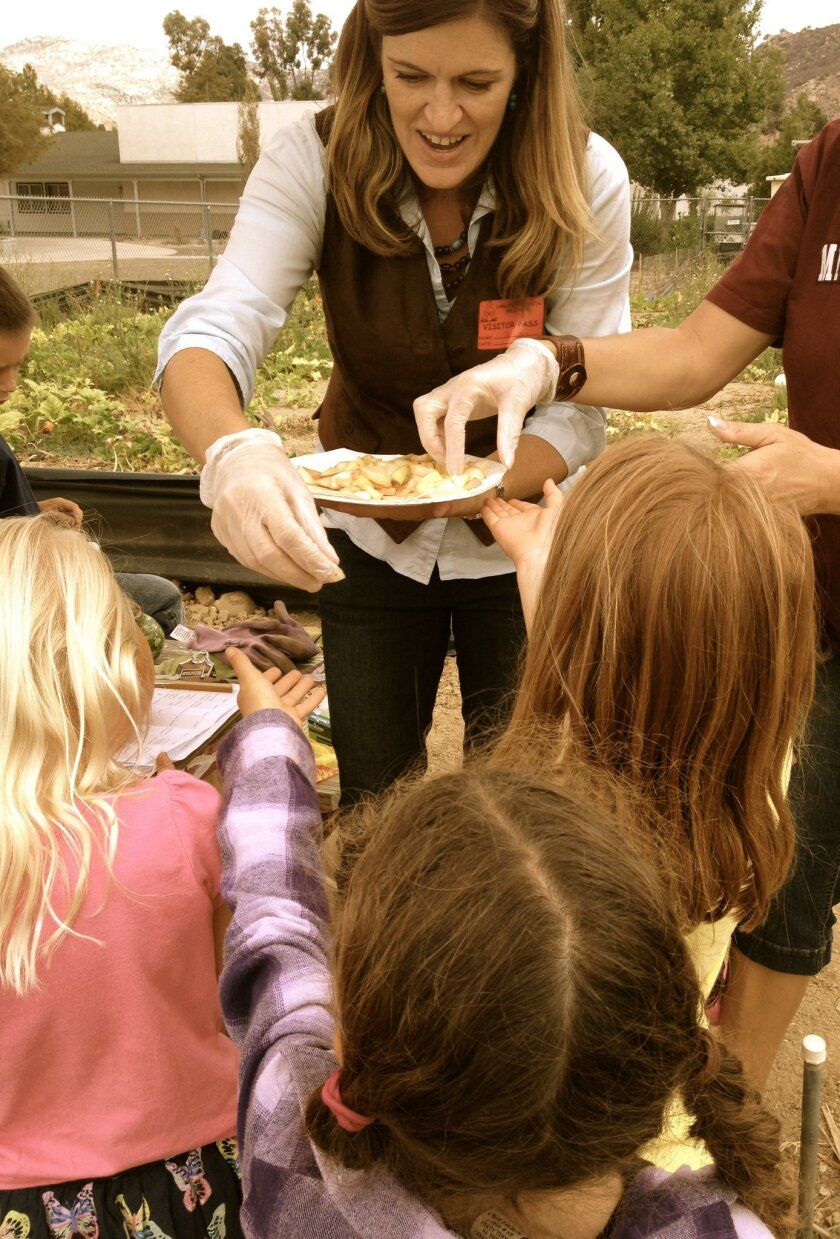 Parent volunteer Christina Knight serves food from Cafe Merlot in Rancho Bernardo to San Pasqual Elementary students during Harvest Day.