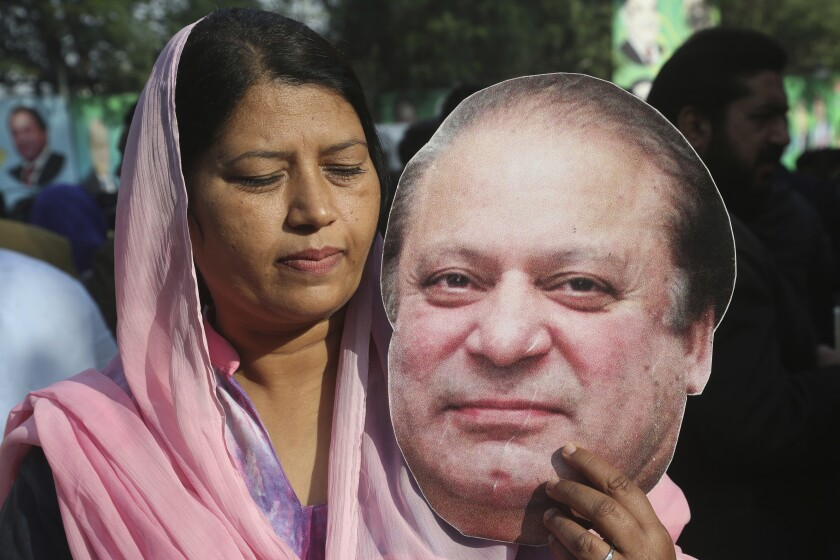 A supporter of former Pakistani Prime Minister Nawaz Sharif holds a picture of him at an airport in Lahore on Tuesday.