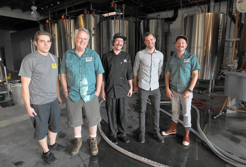 Co-owner Greg Nylen, second from left, and employees of Barley Forge Brewing Co. in Costa Mesa stand in front of its brew tanks soon after the location opened in 2014.