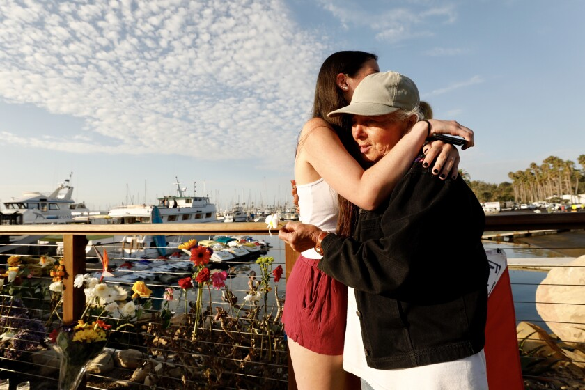 Olivia, left, sister of a female crew member who died in the boat fire, hugs Jennifer Stafford, who placed flowers at a memorial at the Santa Barbara Harbor.