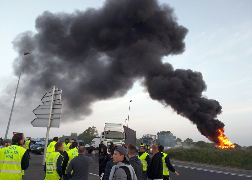 "Union activists guard a traffic circle near the Normandie Bridge outside of Le Havre where a pile of burning tires gas thrown up a big cloud of smoke during a blockade action, Thursday, May 26, 2016. French Prime Minister Manuel Valls says he is open to ""improvements and modifications"" in a labor bill that has sparked intensifying strikes and protests, but will not abandon it. (AP Photo/Raphael Satter)"