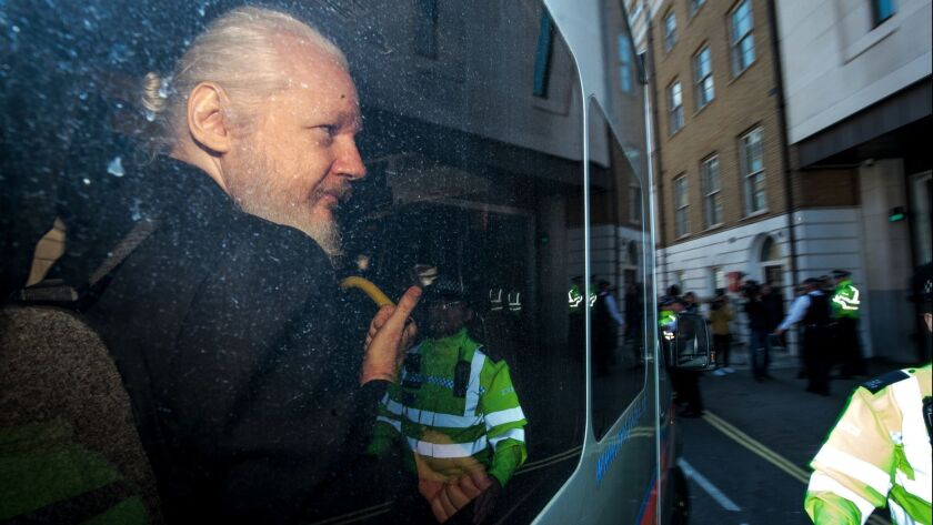 Julian Assange gestures to the media from a police vehicle on his arrival at Westminster Magistrates court in London, England on April 11.