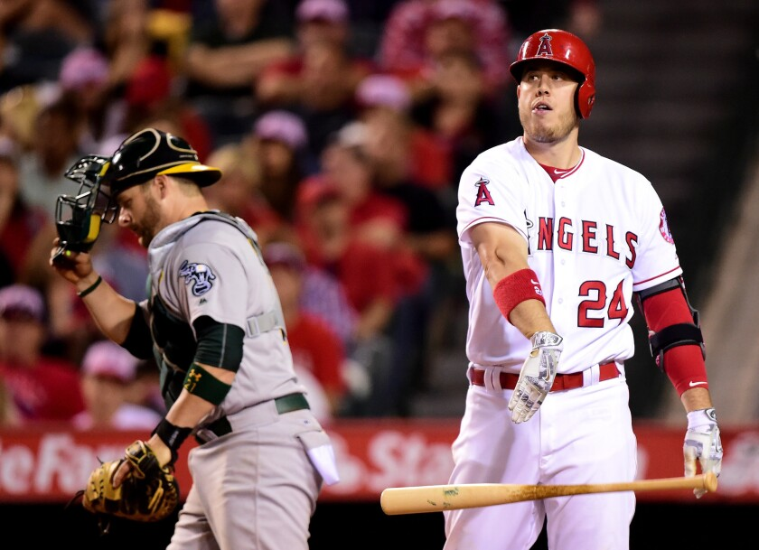 Angels first baseman C.J. Cron (24) tosses his bat in front of Athletics catcher Stephen Vogt after striking out in the seventh inning.