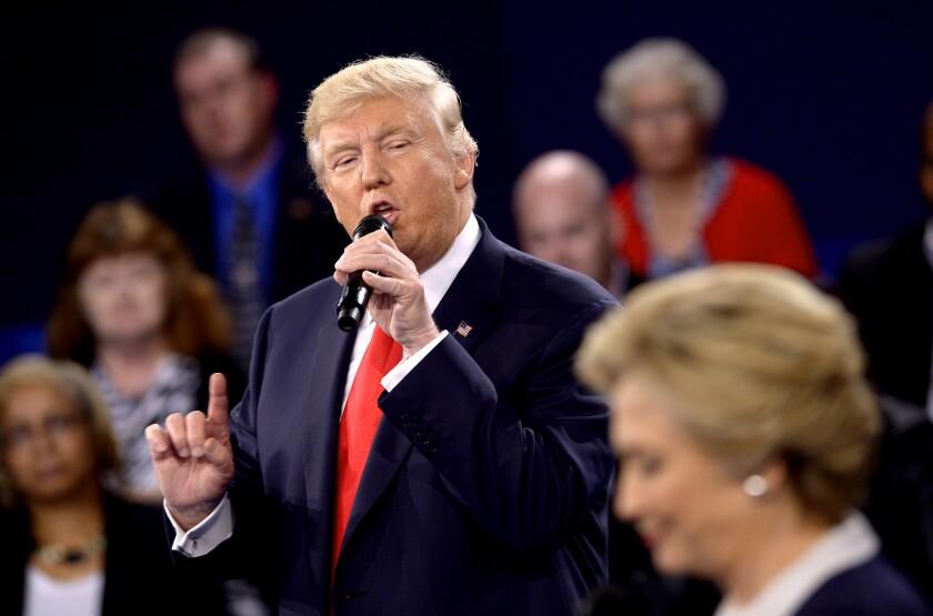 Donald Trump speaks as  Hillary Clinton listens.