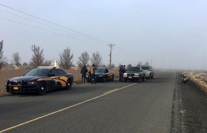 Authorities wait near the Malheur National Wildlife Refuge, Thursday, Feb. 11, 2016, near Burns, Ore. The last four armed occupiers of the national wildlife refuge in eastern Oregon said they would turn themselves in Thursday morning, after law officers surrounded them in a tense standoff.  (AP Pho