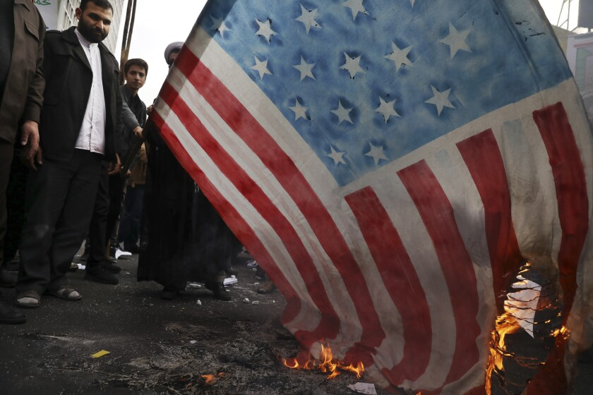 Demonstrators set fire to a rendition of the U.S. flag during a rally in front of the former U.S. Embassy in Tehran on Monday.