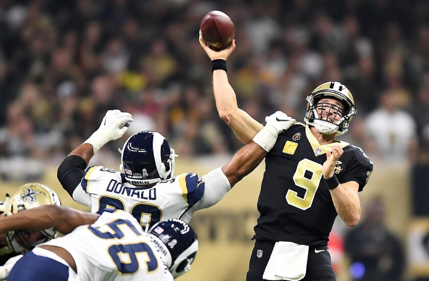 The Rams' Aaron Donald gets an arm on New Orleans Saints quarterback Drew Brees at the Mercedes Benz Superdome in New Orleans on Sunday.